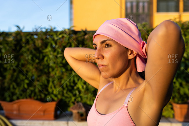 Young brunette woman stretching after training wearing the pink headscarf, symbol of a woman's fight against breast cancer.