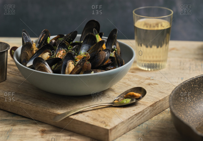 Bowl of steamed mussels on a table with a glass of wine