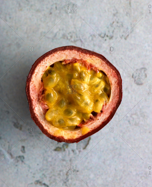 Passion fruit half on light surface
