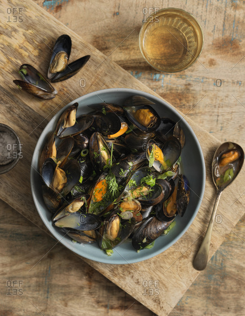 Overhead view of steamed mussels with a glass of wine on wooden table