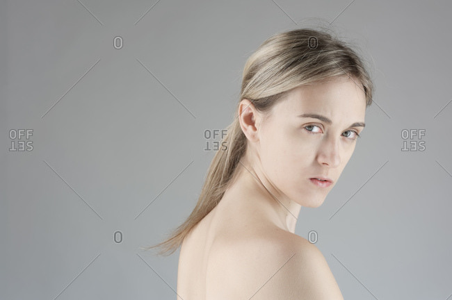 Nude young woman on grey background