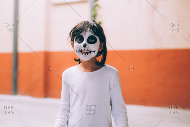 Girl with Halloween face paint, smiling