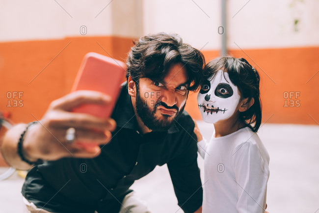 Girl and father taking Halloween selfie