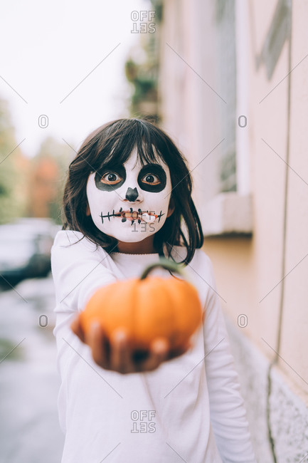 Girl at Halloween with face paint, holding a small pumpkin