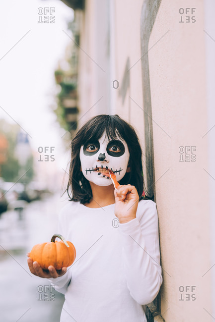 Girl with face paint, eating Halloween candy