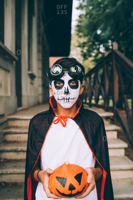 Boy in in Halloween costume with Jack-O-Lantern