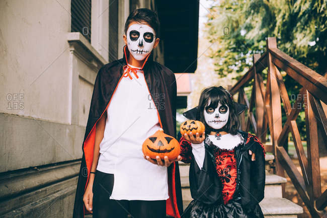 Brother and sister in Halloween costumes with pumpkins