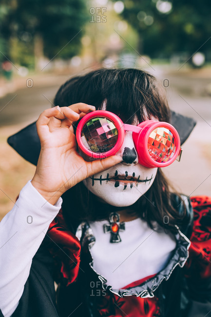 Girl wearing Halloween costume with face paint and goggles