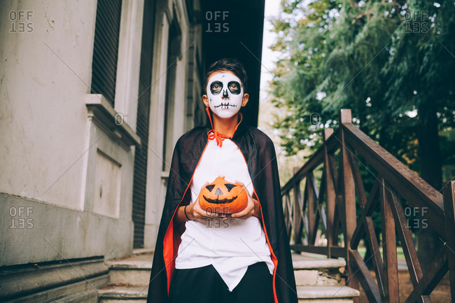 Boy in Halloween costume, holding Jack-O-Lantern