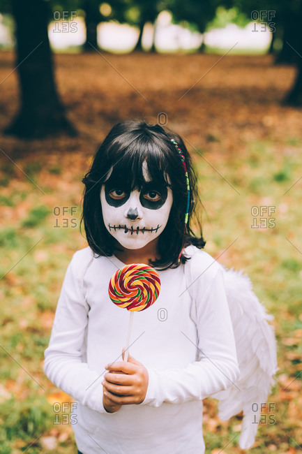 Girl in Halloween costume with lollipop