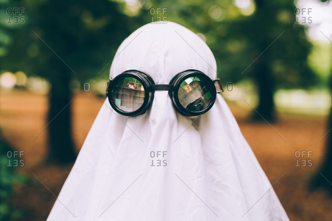 Child wearing sheet and goggles ghost Halloween