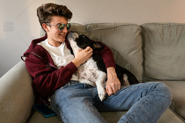 Teen boy wearing sunglasses relaxing on sofa with dog
