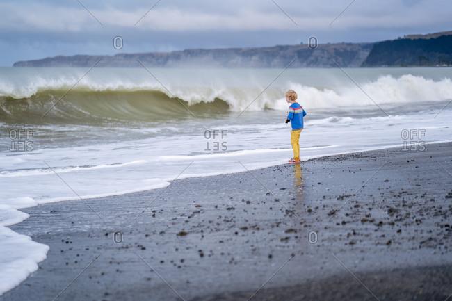 Little boy watching fierce waves roll into the beach shore