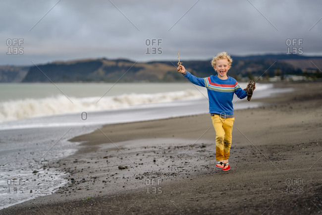 Happy little boy running on beach with sticks and driftwood