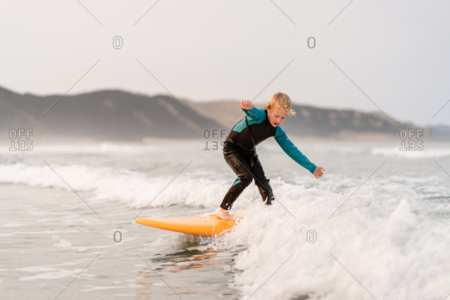 Little blonde boy riding a wave on a yellow surfboard