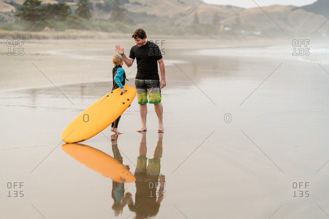 Father high-fiving son after surfing