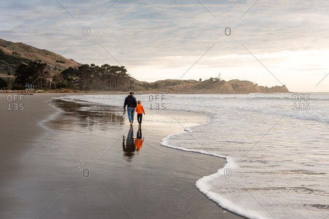 Father and son walking barefoot on beach together