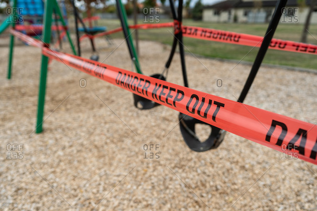 Red tape around swings at a playground