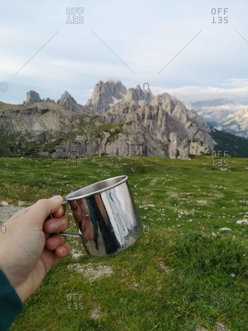 Hand holds camping cup, mountains in the background