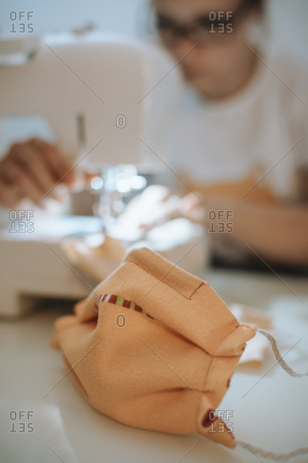 Woman sewing face mask for corona covid pandemic with sewing machine,