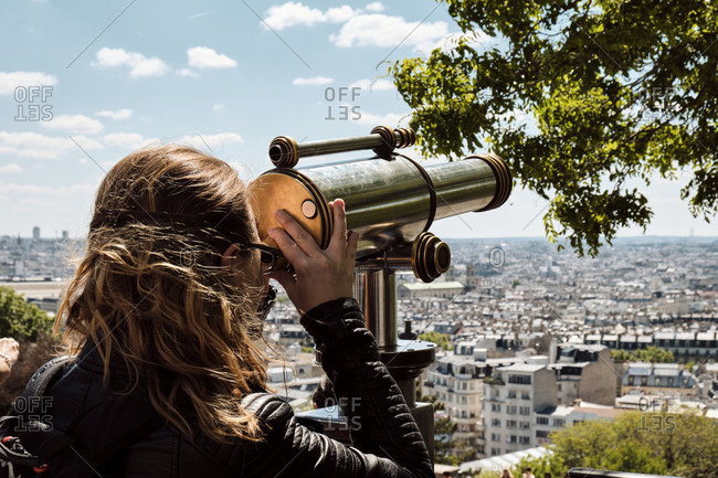 Europe, France, Paris, Montmartre, Sacre Coeur, Woman looking through telescope at Paris,