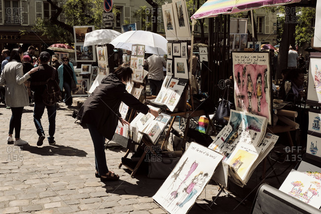 May 16, 2019: Europe, France, Paris, Montmartre, Artists painting and selling artworks on street, Woman looking at pictures