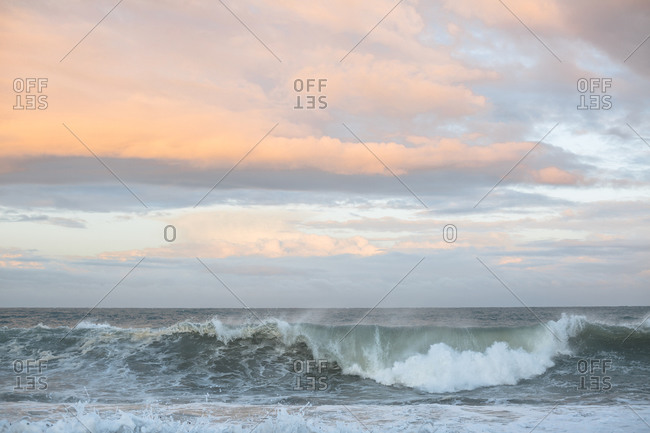 Waves breaking on the beach during dramatic sunset