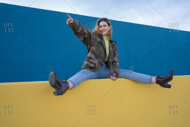 Portrait of a young woman in a military jacket sitting on a wall while she spreads her legs pointing to one side