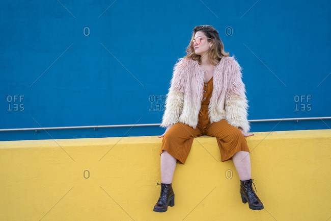 Young woman in a military jacket and sunglasses sitting on a yellow wall with a blue wall