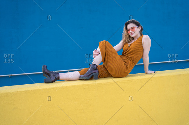 Young blonde woman feels happy sitting on a yellow wall with a blue wall in the background