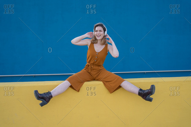 Young blonde woman enjoys listening to music in headphones sitting on a yellow wall with a blue wall in the background