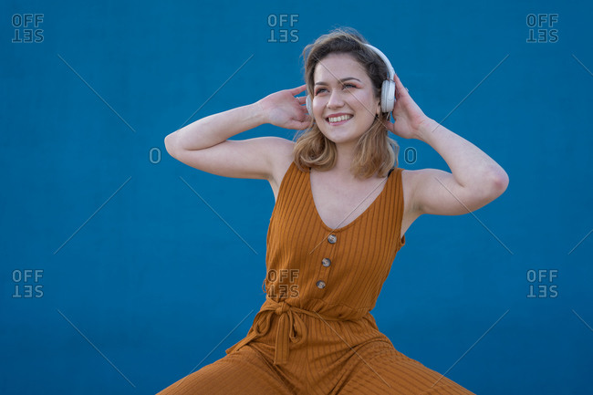 Happy blonde woman enjoys listening to music in headphones with a blue wall in the background