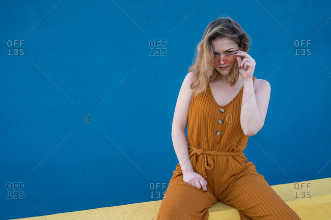 Young blonde woman looking over her sunglasses while sitting on a yellow wall with a blue wall in the background