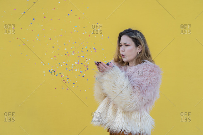 Young blonde woman in pink jacket plays with confetti with a yellow wall in the background