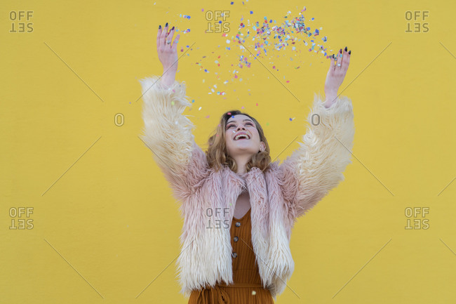 Young blonde woman with pink hair jacket plays with the confetti with a yellow wall in the background