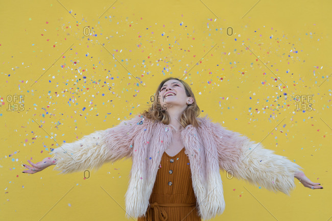 Young blonde woman with pink hair jacket smiles under a rain of confetti with a yellow wall in the background