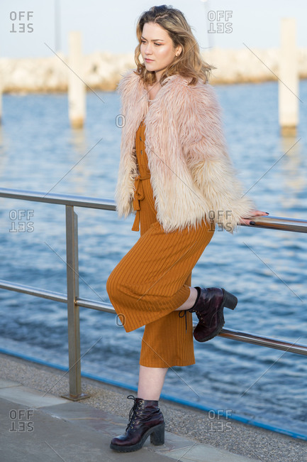 Young blonde woman with pink hair jacket leaning against the railing of the marina looking distractedly at the floor