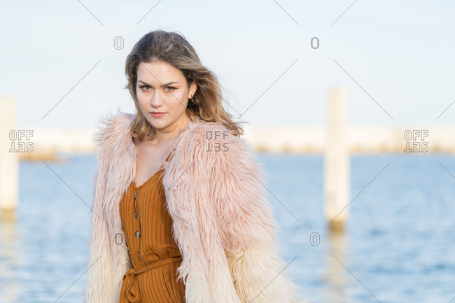 Young woman with pink hair jacket leaning against the railing of the marina looking defiantly into the camera