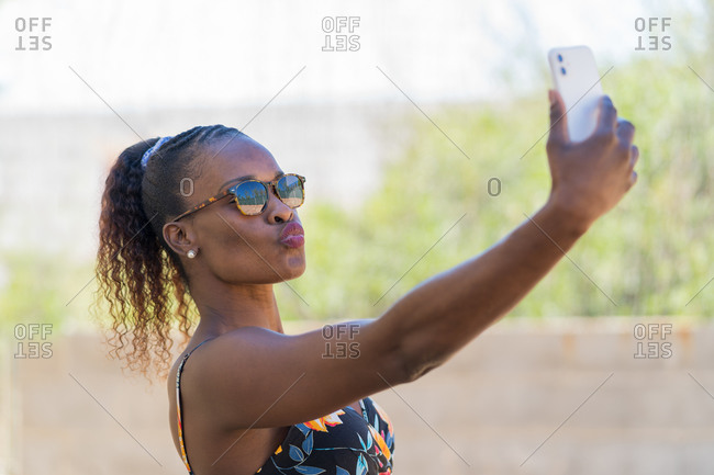 Self portrait of beautiful afro American woman wearing colorful dress and sunglasses. Selfie Concept.
