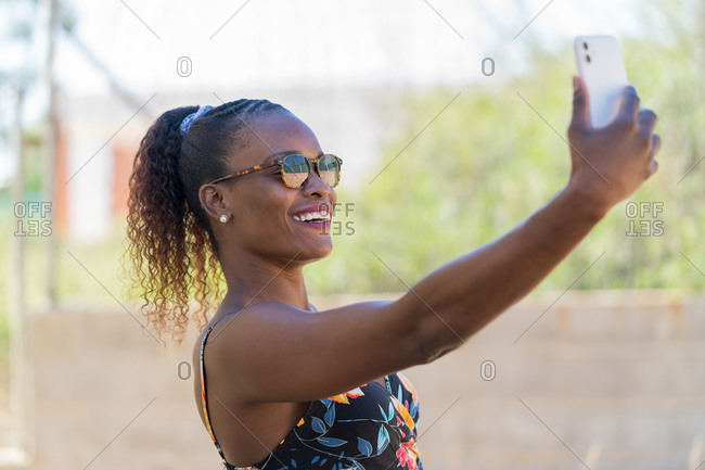 Self portrait of happy afro American woman wearing colorful dress and sunglasses. Selfie Concept.