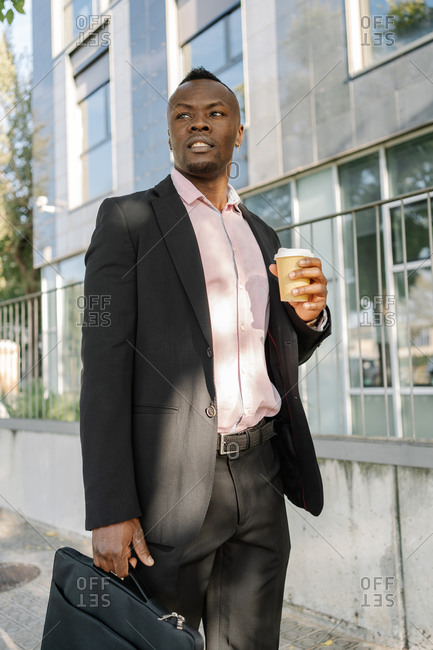 African American businessman walking around the city with his briefcase holding a glass of coffee