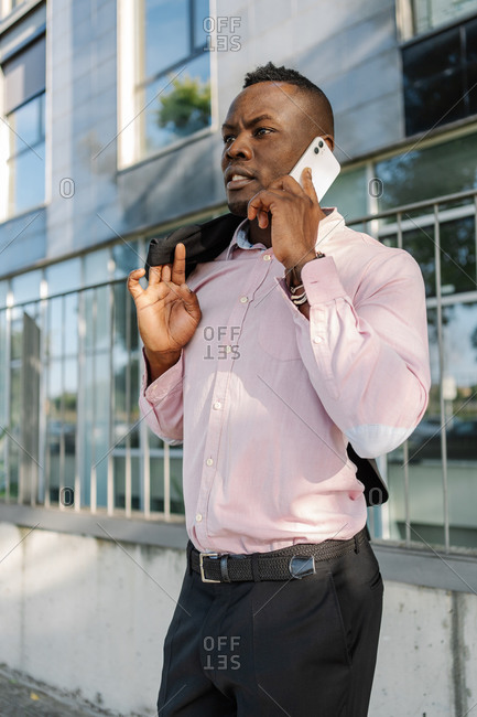 Portrait of a black young confident businessman using cell phone in city