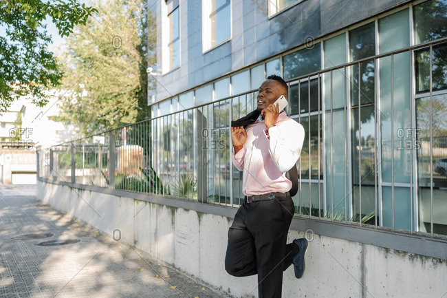 African American young confident businessman using cell phone in city