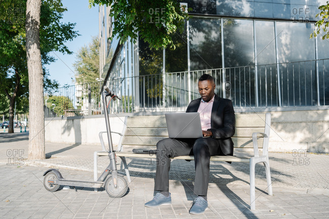 Portrait of an African American businessman sitting on a bench wile working on a laptop