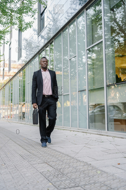 Full length portrait of an afro young businessman walking in the city