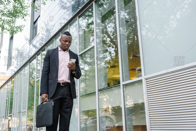 Portrait of an afro businessman looking at his phone while walking to the office