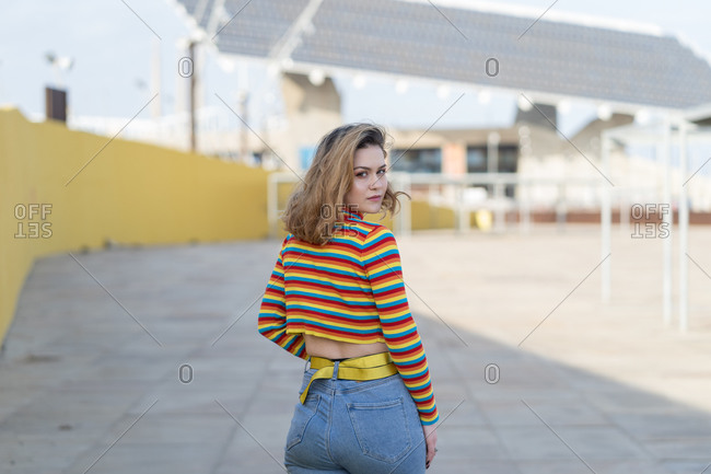 Rear view of young woman looking over shoulder dressed in a multicolored striped sweater