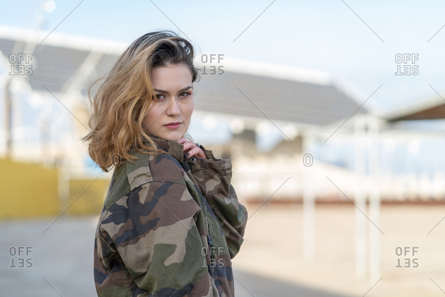 Portrait of a young woman in a military jacket looking over her shoulder at the camera