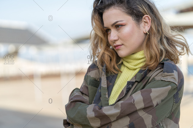 Portrait of a young woman dressed in a military jacket who looks to the side with tenderness