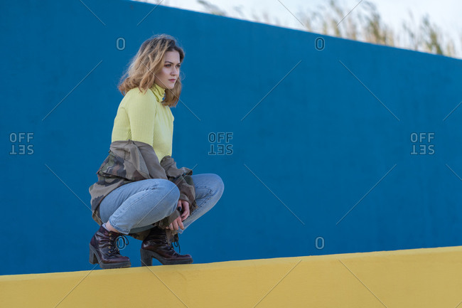 Young woman dressed in a military jacket sits squatting on a yellow wall with an absent-minded look